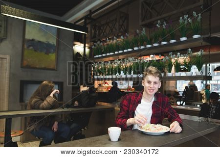 A Beautiful Young Man Eating Salad With A Fork In A Cafe. Student Dishes With Salad In A Restaurant.