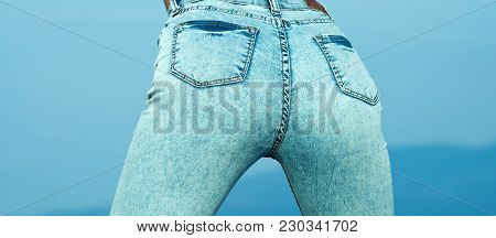 Pretty Women 's Ass In Tight Jeans On Blue Background. Fit Female Butt In Jeans. Young Sexy Woman Is
