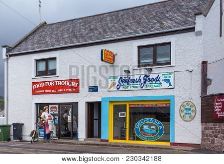 Ullapool, Scotland - June 8, 2012: White Houses In Street Are Butcher And Fish Shop. Colorful Advert