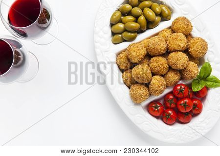 Healthy Italian Appetizer Platter With Risotto Balls Arancini , Green Olives , Tomato And Red Wine.