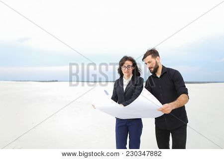 Designer Man And Representative Of Investment Company Woman Holding Whatman Paper With Plan, People