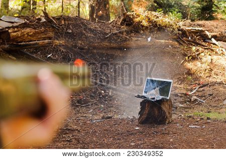 Angry person destroying a laptop with a shotgun