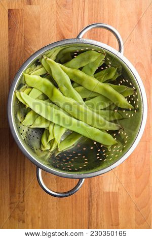 Cooked green string beans pods in colander.