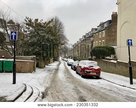 HAMPSTEAD, LONDON - FEBRUARY 28, 2018: People travel with care in slipper conditions caused by Storm Emma, also known as the 'Beast from the East' weather front in Hampstead, North London, UK.
