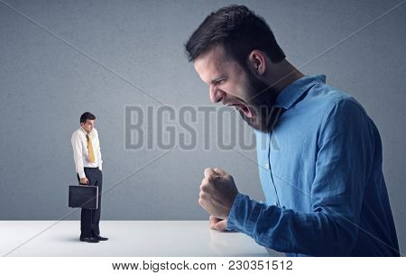 Young professional businessman being angry with an other miniature businessman