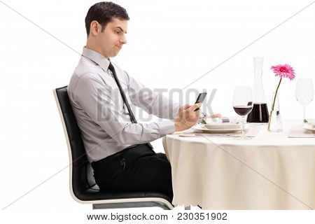 Disappointed young man seated at a restaurant table looking at his phone isolated on white background