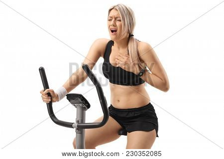 Young woman riding an exercise bike and having a heart attack isolated on white background