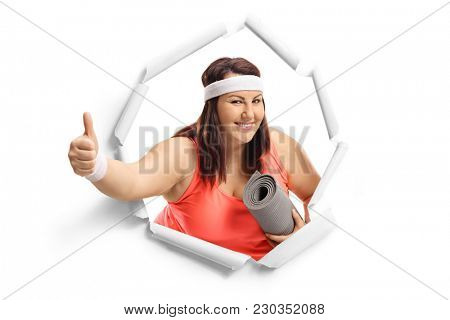 Overweight woman with an exercise mat breaking through paper and making a thumb up gesture