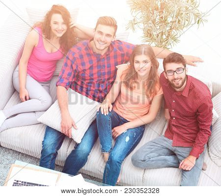 four friends laugh, sitting on the sofa