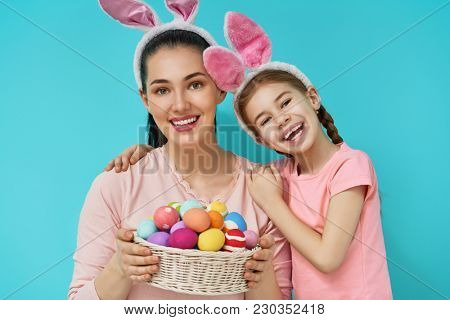 Happy holiday! Mother and her daughter with painting eggs. Family preparing for Easter. Cute little child girl is wearing bunny ears.