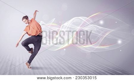 A  young hip hop dancer dancing contemporary urban street dance in front of grey wall background with smokey lines and glitter concept.
