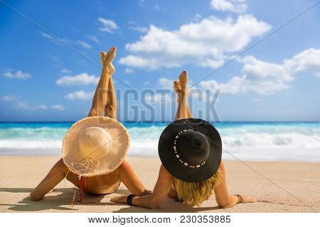 Two women with strasw hat suntanning