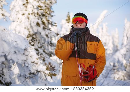 A young guy is a snowboarder with his snowboard on top of a mountain in a bright jacket and a protective mask. Sheresh. Russia.