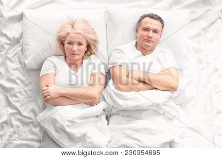 Senior couple with problem in relationship on bed