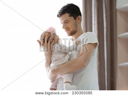 Young father with his cute little baby near window at home
