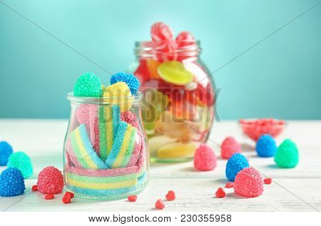 Glassware with different chewy candies on table against color background