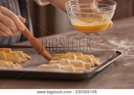Woman spreading egg yolk onto croissants at table