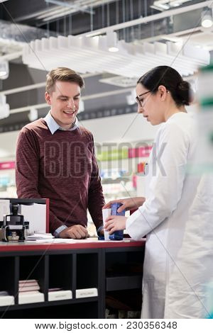 Portrait of a handsome young man and happy customer listening to the recommendations and the advice of a reliable female pharmacist in a contemporary drugstore