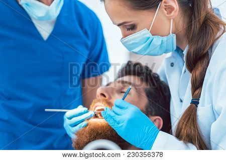 Side view of a reliable female dentist using sterile instruments and blue surgical gloves, while cleaning the teeth of a patient in the dental office of a modern clinic