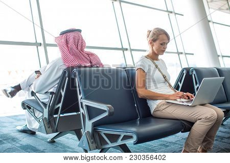 Young female passenger at the airport, waiting for her delayed flight, doing some work on her computer