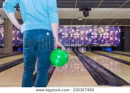 man concentrating before his throw on a game of bowling with a green bowling ball