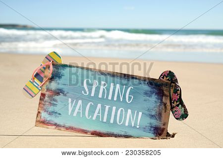closeup of a rustic signboard with the text spring vacation written in it and some colorful flip-flops, on the sand of a quiet beach, with the ocean in the background