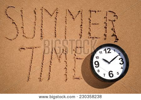 high angle view of a clock and the text summer time written on the wet sand of the seashore of a beach