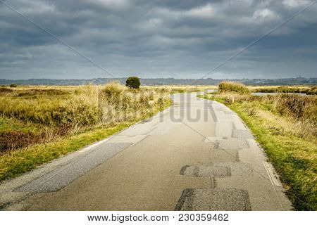 Road in the Guerande salt marshes, France. Sunlight and moody sky.