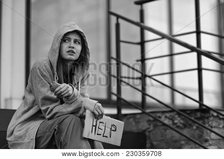 Homeless poor woman holding piece of cardboard with word HELP outdoors