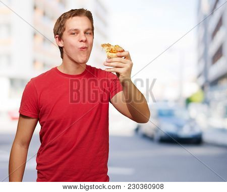 portrait of young man eating pizza portion against a modern building