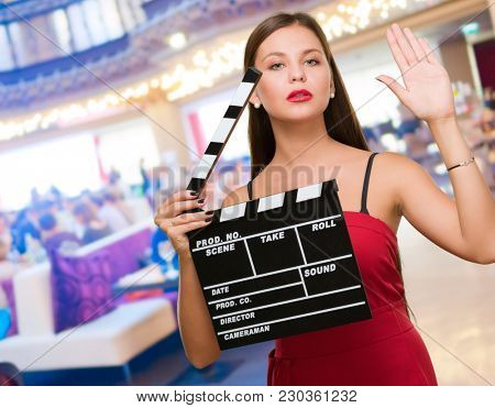 Young Woman Holding Clapper Board at a restaurant