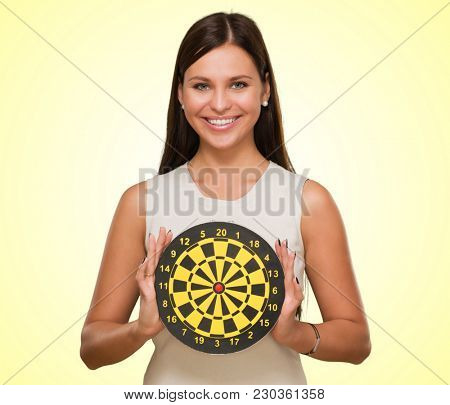 Portrait Of A Young Woman Holding Bull's Eye Smiling against a yellow background