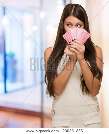 Pretty Young Woman Holding Playing Cards at a hotel