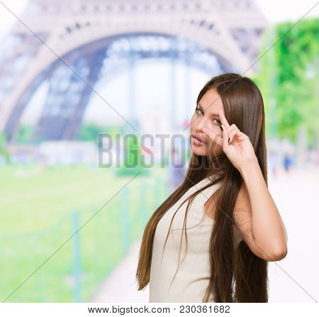 Beautiful Smiling Woman Showing Two Fingers In Front Of Eye at a park