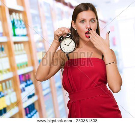 Shocked Woman Holding Alarm Clock, indoor