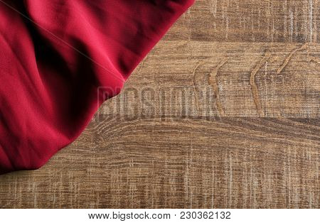 Synthetic textile on wooden background. Fabric texture