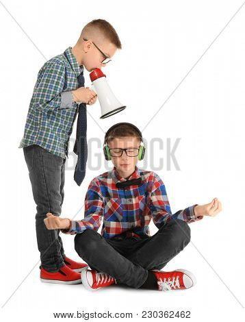 Cute little boy meditating and ignoring his friend with megaphone, on white background