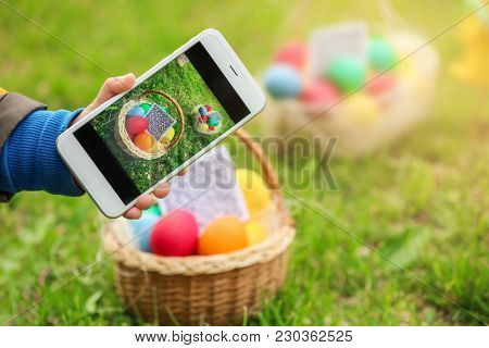 Little boy scanning QR Code in basket with colorful eggs at park. Easter hunt concept