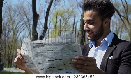 Man Sits On Chair Near Table And Reading Newspaper.  Guy Has Beard, Short Hair And Dimples. Man Dres