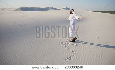 Handsome Arabian Uae Sheikh Man Dances On Spot And Drives Feet Along Soft White Sand In Middle Of Bo