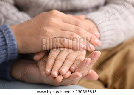 Woman and her adopted child, closeup of hands