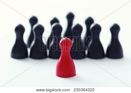 Red pawn in front of black ones on white background. Difference and uniqueness concept