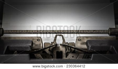 Typewriter With A Blank White Paper. Writing On Typewriter. Black Background.