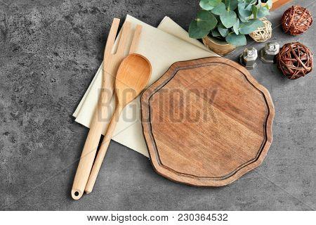 Wooden cooking utensils on grey background