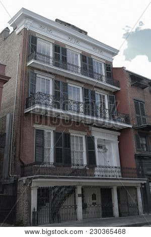 New Orleans Townhouse With Wrought Iron Balcony And Handrails Taken On A Summer Day In The French Qu