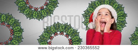 Digital composite of Girl against grey background with Santa hat amazed and surprised looking up and holly boughs