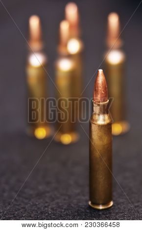 Five .223 Caliber Rounds On A Black Background