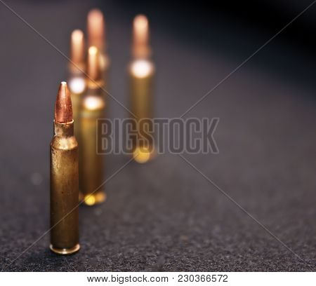 Five .223 Caliber Rounds On A Black Background With Room For The Text On The Right Side