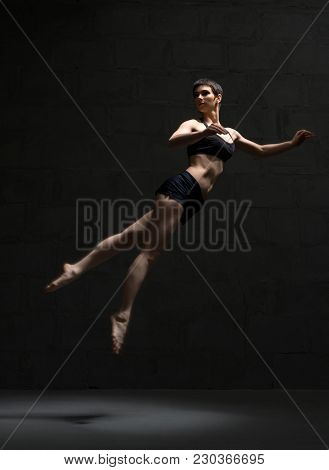 Ballet Dancer With Shot Haircut In Top And Shorts Jumping Gracefully In Dark Room