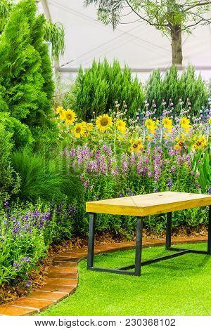 Wood Chair In Cozy Flower Garden On Summer.